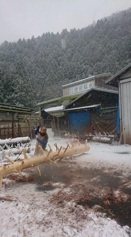 雪の中、水圧を使い皮むき作業